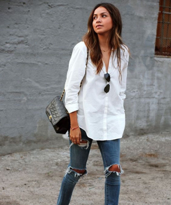 Woman wearing a white button down shirt and distressed denim jeans