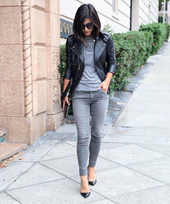 Woman walking down the street wearing a grey tshirt and a leather jacket